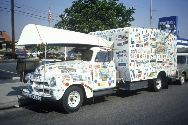 En lastbil som täckas med bildekaler, bär en kanot överst, den Culver staden, Kalifornien arkivfoto