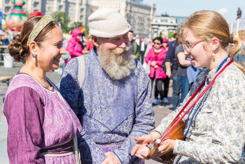 En le äldre man med ett grått skägg i en nationell dräkt står med två unga kvinnor fotografering för bildbyråer