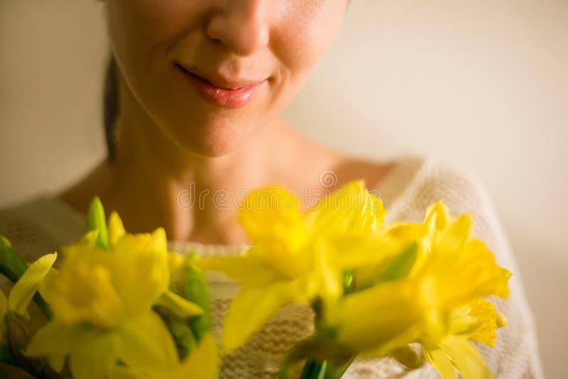 En le flicka med en bukett av den gula våren blommar, pingstliljan arkivfoton