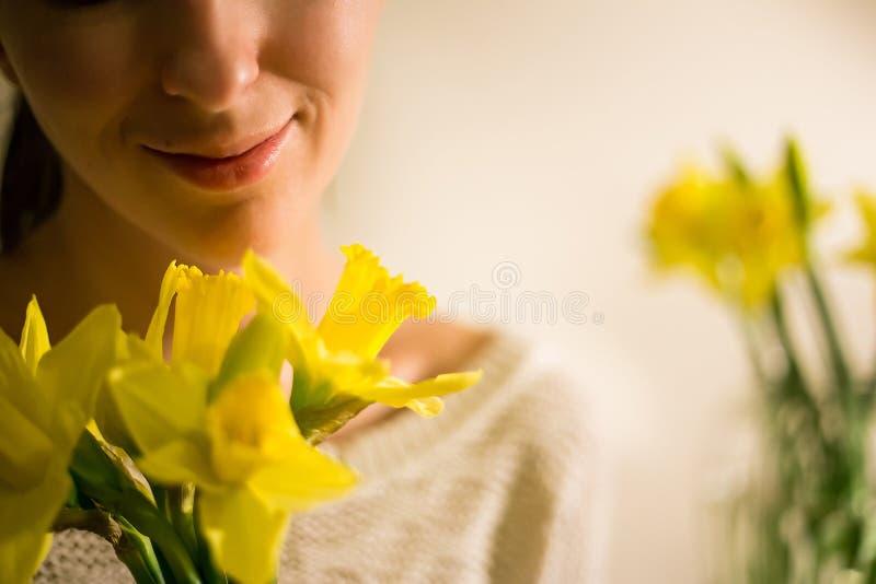 En le flicka med en bukett av den gula våren blommar, pingstliljan royaltyfria foton