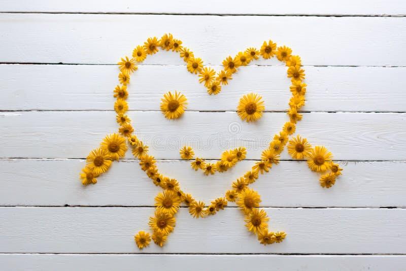 En le hjärta med armar och ben som göras av gula blommor arkivbilder