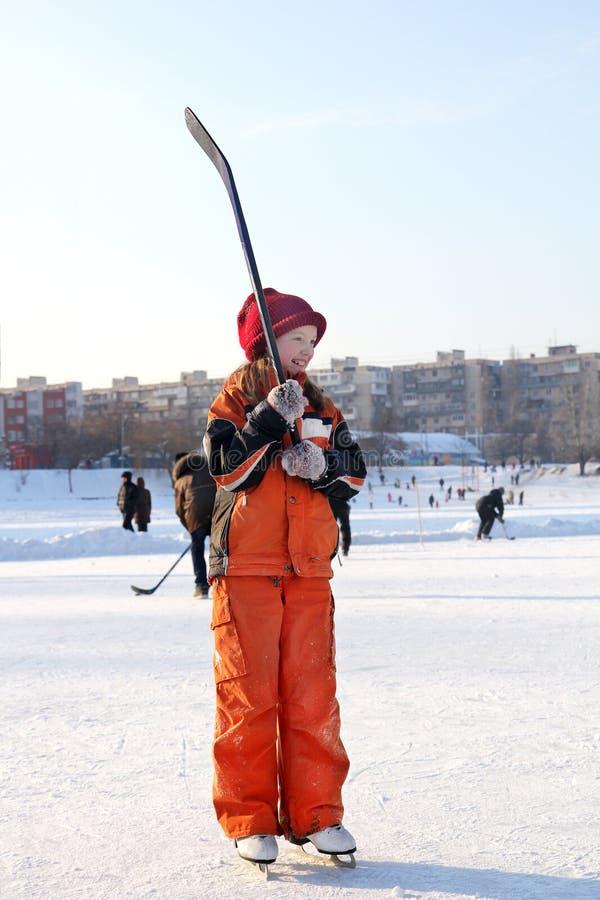 En le liten flicka är på en åka skridskor isbana i skridskor med en hockeypinne i hennes hand arkivbilder