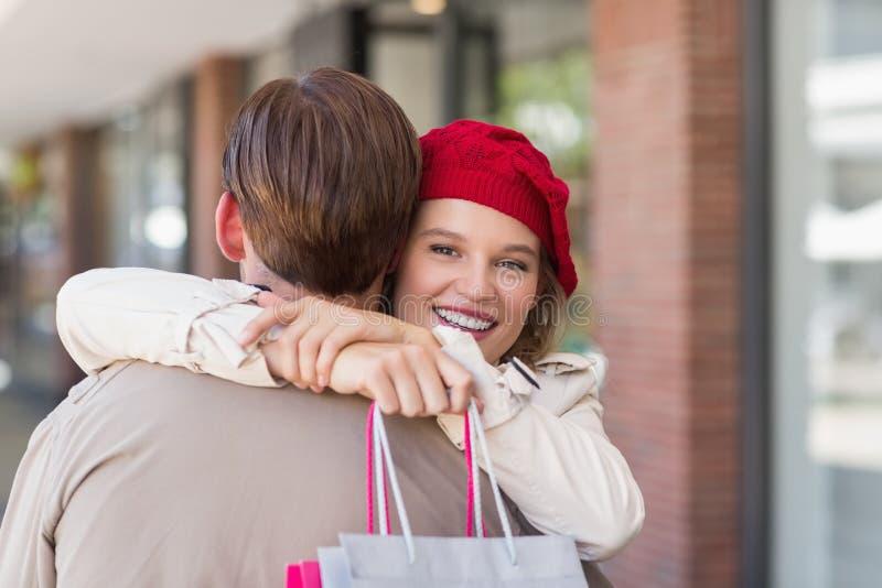 En le lycklig kvinna som kramar hennes pojkvän arkivbild