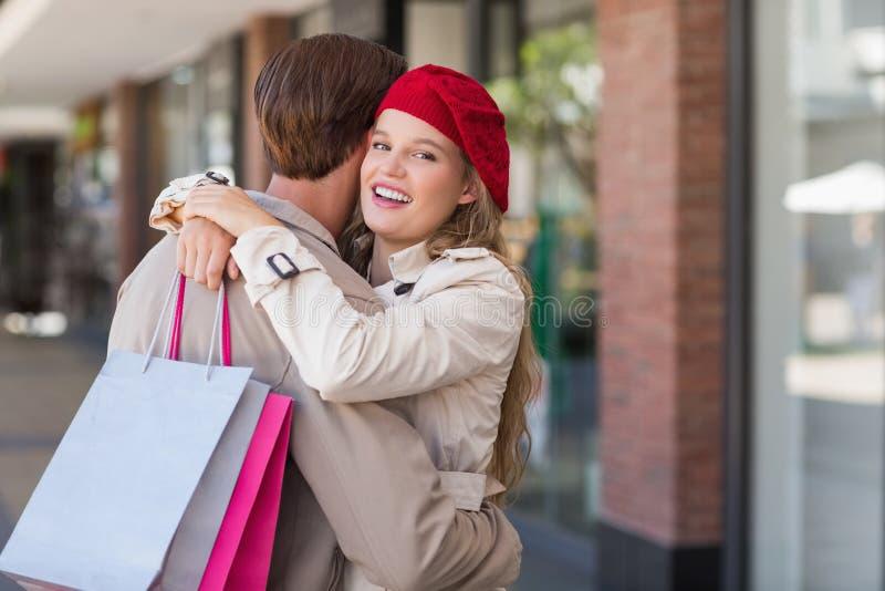 En le lycklig kvinna som kramar hennes pojkvän arkivfoto