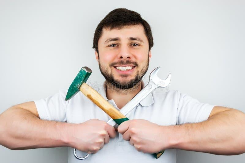 En le lycklig sk?ggig man i en vit t-skjorta med en hammare och en skiftnyckel som p? tv?ren rymmer dem royaltyfri fotografi