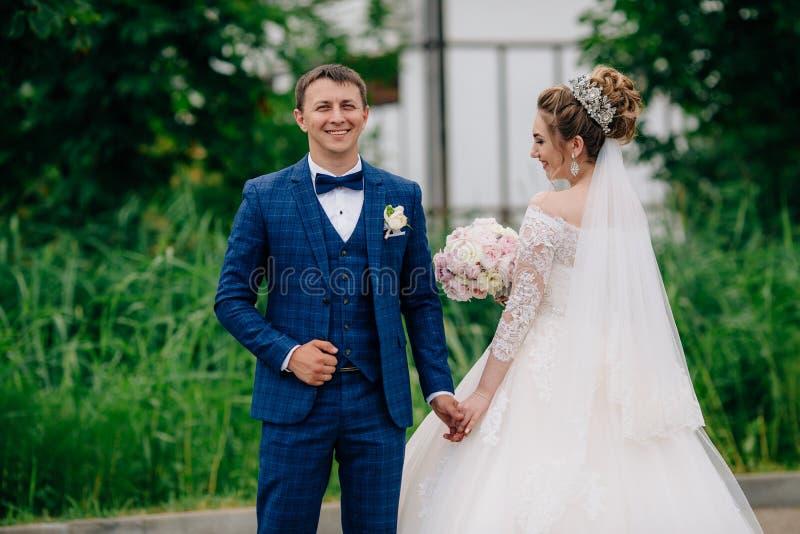 En le man i en stilfull affärsdräkt ler och rymmer hans brud, som står i bröllopsklänningen med henne tillbaka arkivbild