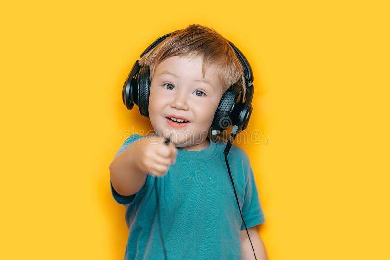 En le pojke att koppla från hans headphone och showpropp till kameran på isolerad gul bakgrund royaltyfri fotografi