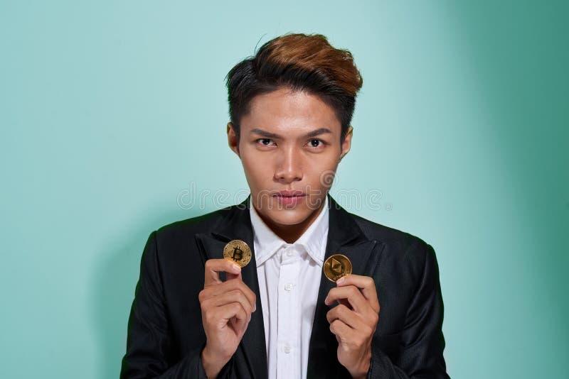 En le skjorta och ett omslag visar två guld- bitcoin och en etherium för ung man som iklädd isoleras över grå bakgrund royaltyfri foto