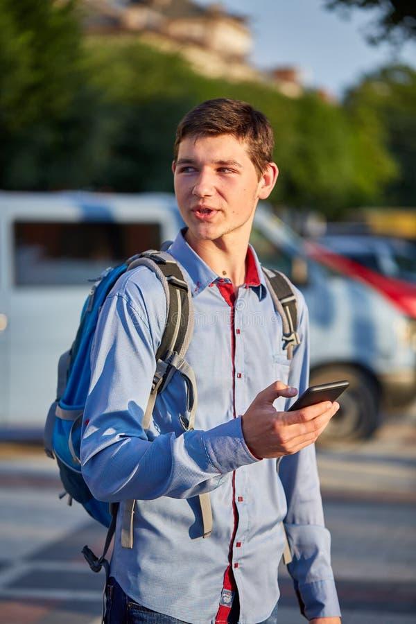 En le ung man med en smartphone i hans händer som går runt om staden på bakgrunden av gatan, lodlinje arkivfoto