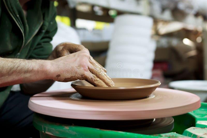 En ledar- ceramist med 13 år av erfarenhet gör plattan från röd lera på keramikers hjul, på ett ark av partikeln royaltyfria bilder