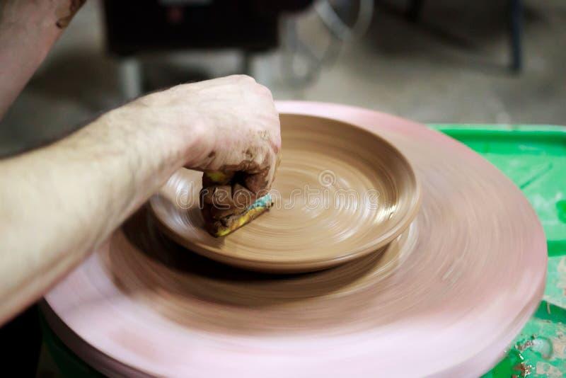 En ledar- ceramist med 13 år av erfarenhet gör plattan från röd lera på keramikers hjul, på ett ark av partikeln fotografering för bildbyråer