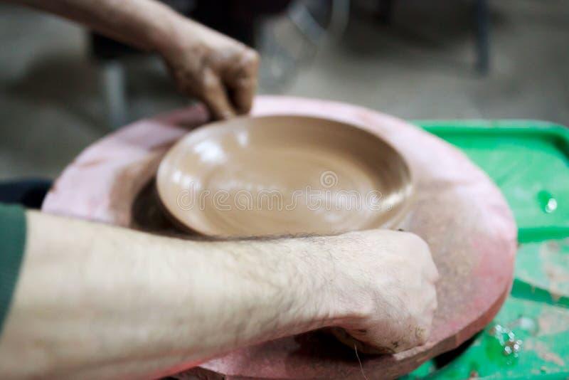 En ledar- ceramist med 13 år av erfarenhet gjorde plattan från röd lera på keramikers hjul, på ett ark av spånskivan arkivfoton
