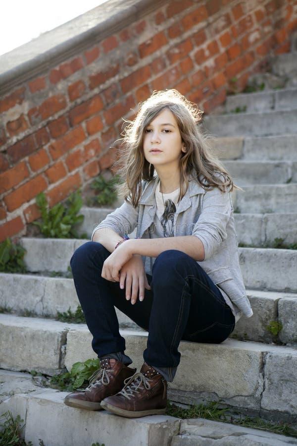 En ledsen flicka med långt hår i jeans av tretton sitter på momenten arkivbild