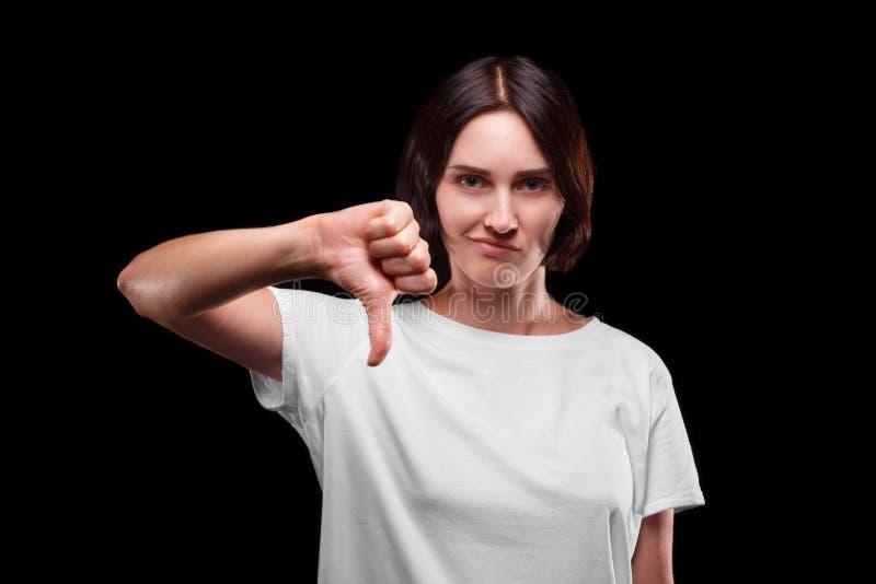 En ledsen flicka som ner visar en tumme En uppriven ung kvinna i en vit T-tröja på en svart bakgrund kopiera avstånd royaltyfria bilder