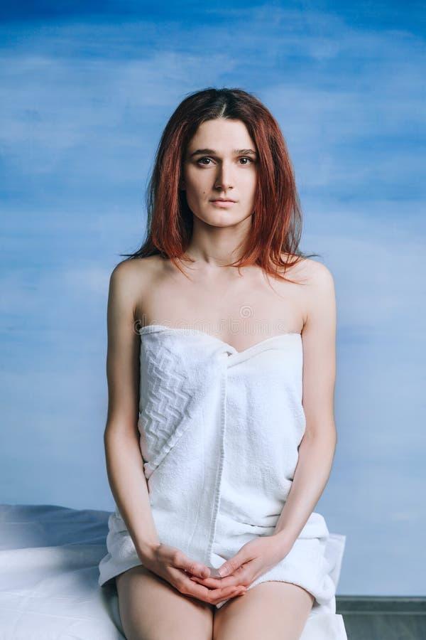 En ledsen härlig ung kvinna sitter på en soffa i en handduk som väntar på en doktors tidsbeställning royaltyfri fotografi