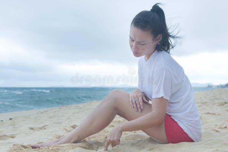 En ledsen kvinna ser ner i sanden med hennes djupa tankar arkivfoton