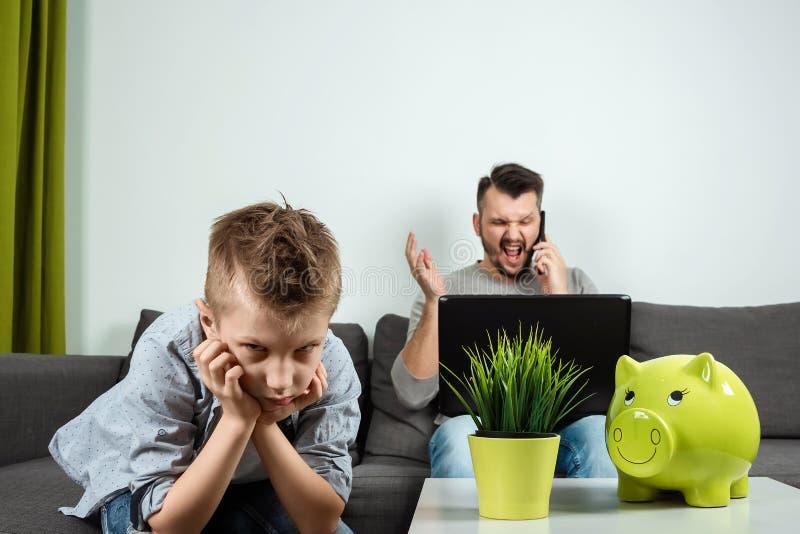 En ledsen pojke ser kameran, medan hans fader arbetar i bakgrunden hemma Begreppet av tid tillsammans, ensamma barn, arkivfoton