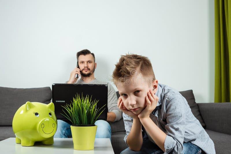 En ledsen pojke ser kameran, medan hans fader arbetar i bakgrunden hemma Begreppet av tid tillsammans, ensamma barn, fotografering för bildbyråer