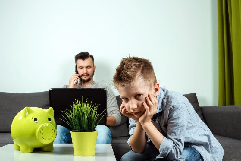 En ledsen pojke ser kameran, medan hans fader arbetar i bakgrunden hemma Begreppet av tid tillsammans, ensamma barn, royaltyfri foto