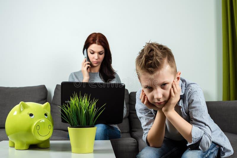 En ledsen pojke ser kameran, medan hans mamma arbetar i bakgrunden hemma Begreppet av tid tillsammans, ensamma barn, arbete arkivfoto