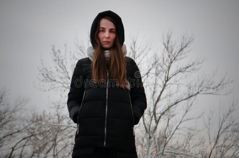 En ledsen ung flicka i en huv i en vinter parkerar royaltyfri fotografi