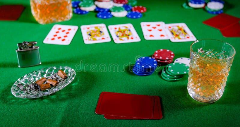 En lek av poker med ett exponeringsglas av whisky royaltyfri foto