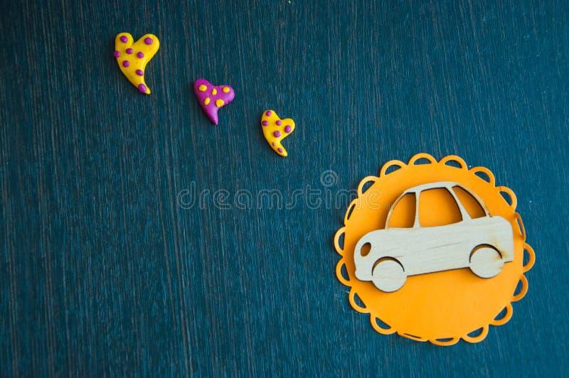 En leksakbil och en ljus hjärta på en trätabell arkivfoton