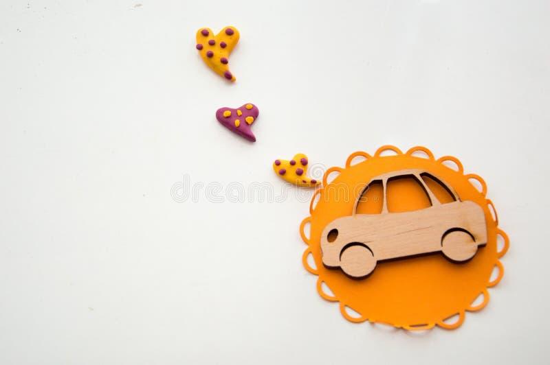 En leksakbil och en ljus hjärta på en trätabell arkivbilder