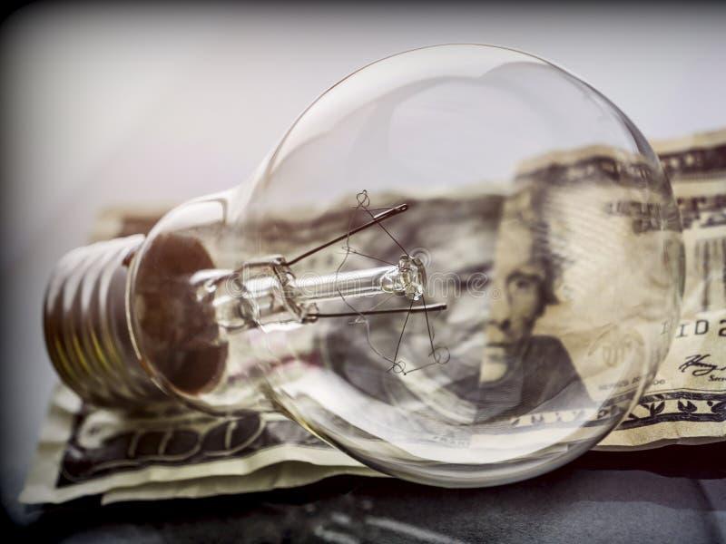 En lightbulb på dollarräkningen, energi - besparingbegrepp arkivfoton