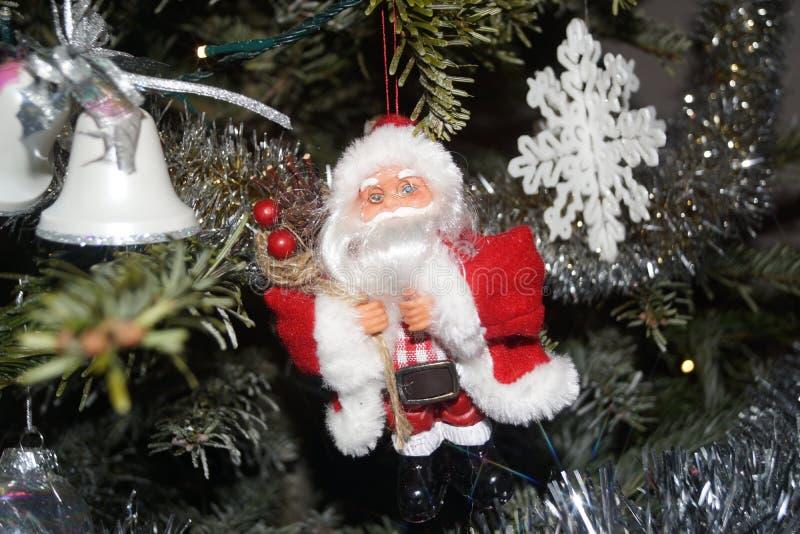 En lilla Santa Claus hängdes på i granträdet, på en sida finns det små klockor och på andra sidanflingan av jul framdel royaltyfri bild