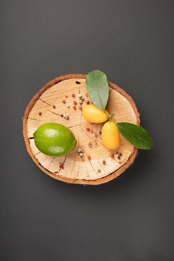 En limefrukt och apelsiner på en träplatta arkivbild