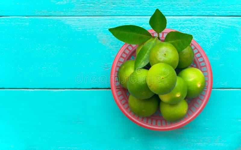 en limefruktcitron i röd hink på blå träbakgrund kopiera avstånd fotografering för bildbyråer