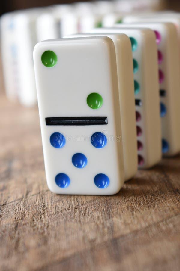 En linje av dominobrickor på trä arkivbild