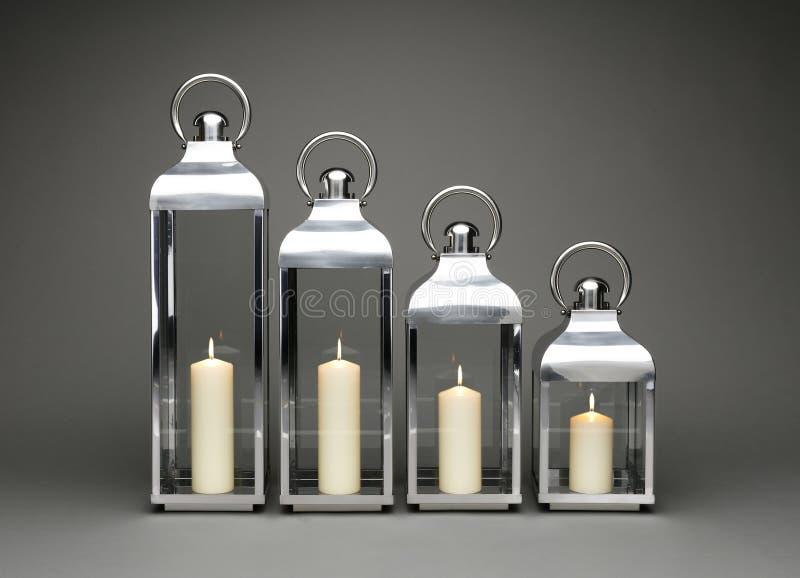 En linje av fyra stearinljus som rymmer lyktor, med tända stearinljus på en grå bakgrund arkivbilder