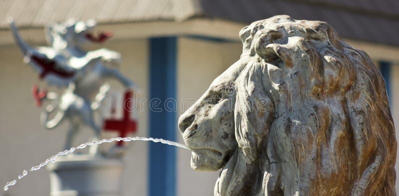 En Lion Statue Shoots en båge av vatten royaltyfri bild