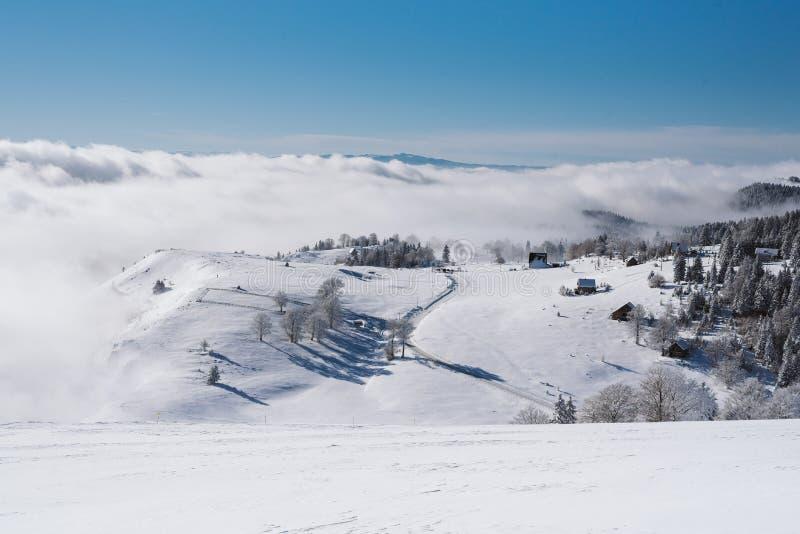 En liten by överst av ett snöig berg med en klar blå himmel på en solig dag royaltyfria foton