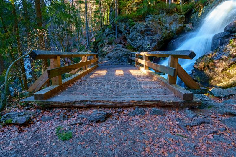 En liten bro framme av en vattenfall arkivbilder