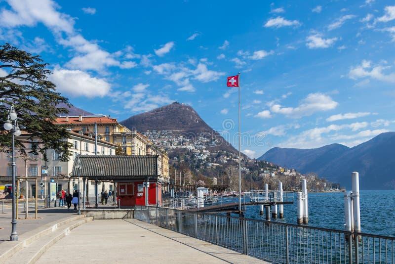 En liten brygga i Lugano med nationsflaggan av Schweiz royaltyfri bild