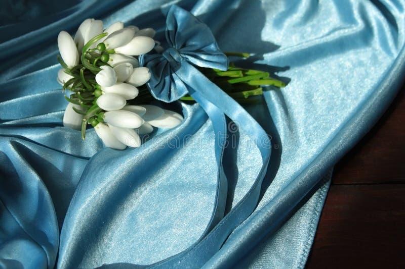 En liten bukett av de första vårblommorna av snödroppar som binds med ett blått siden- band med en pilbåge på en trätabell med et arkivfoto