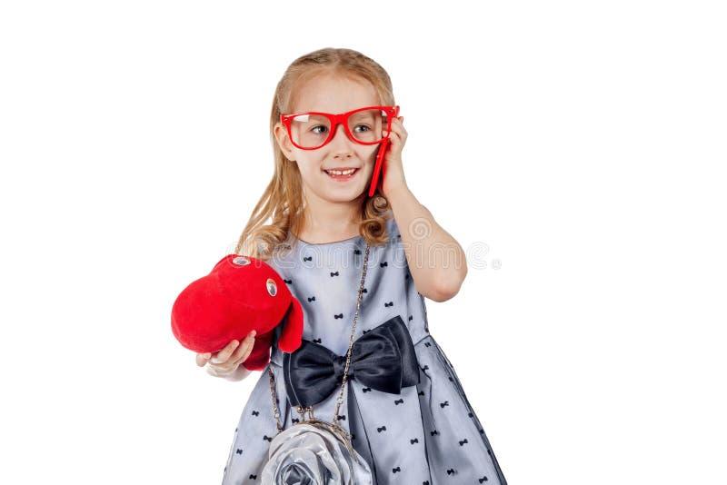 En liten fashionist i röda exponeringsglas talar på telefonen arkivbilder