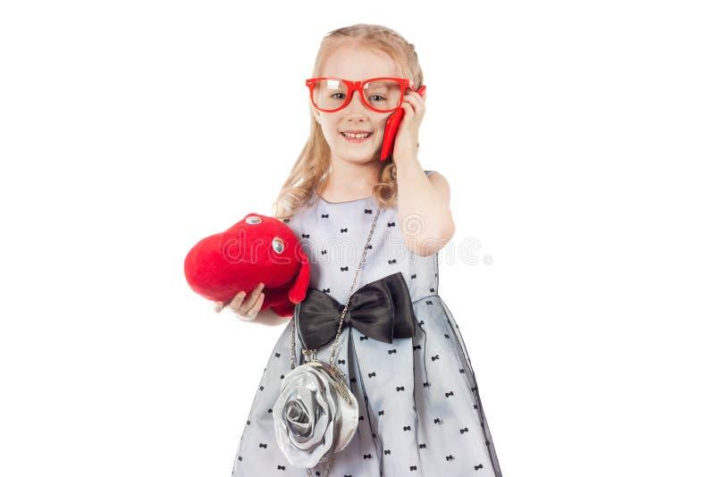 En liten fashionista med en leksakhund i stora röda exponeringsglas arkivbild