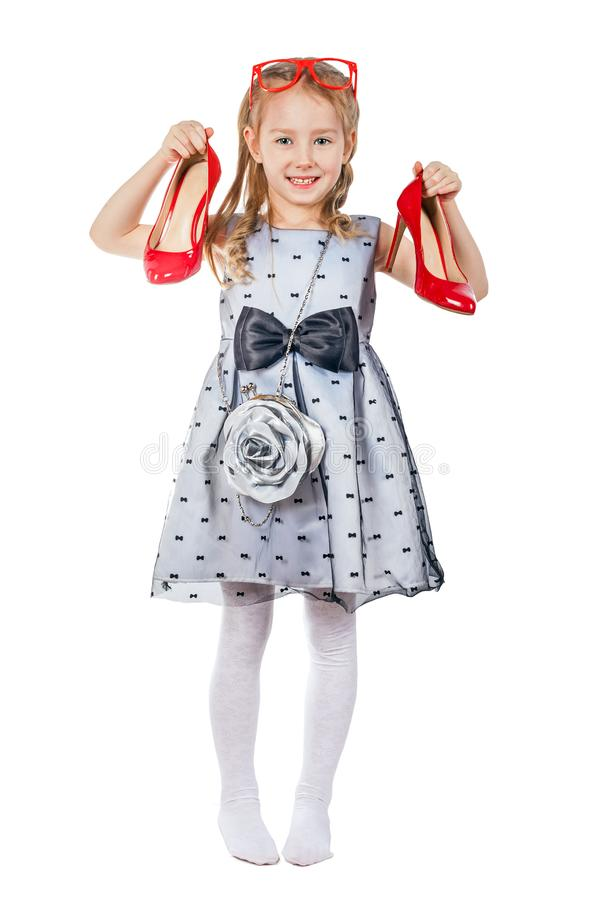 En liten fashionista rymmer röda skor i hennes händer arkivbild