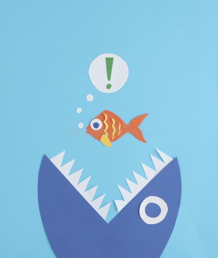 En liten fisk som ätas av en stor fisk royaltyfri foto