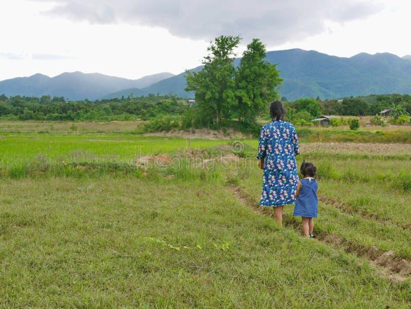 En liten flicka, dotter, som följer med sin mor fotsteg på landsbygden i Thailand arkivbild
