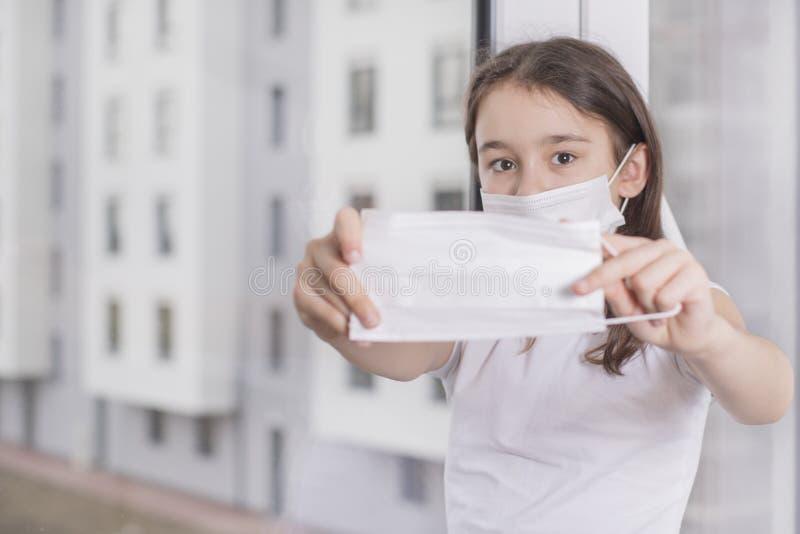 En liten flicka erbjuder sig att bära en skyddsmask för att skydda Covid-19 står nära fönstret Flickan blev sjuk och kan inte gå  arkivfoton