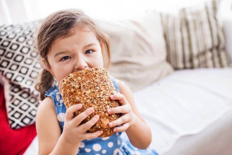 En liten flicka hemma som äter en släntra av bröd royaltyfri bild