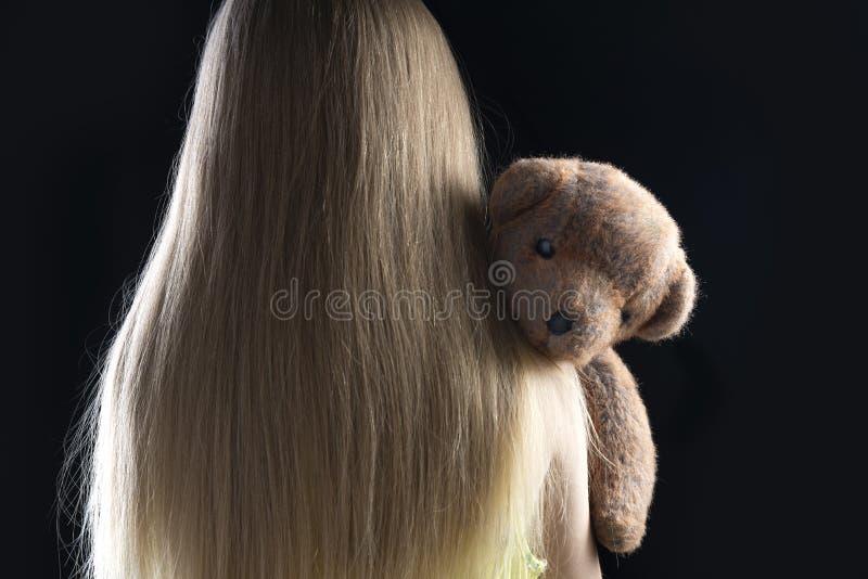 En liten flicka med en björn på axeln på en mörk bakgrund arkivfoto