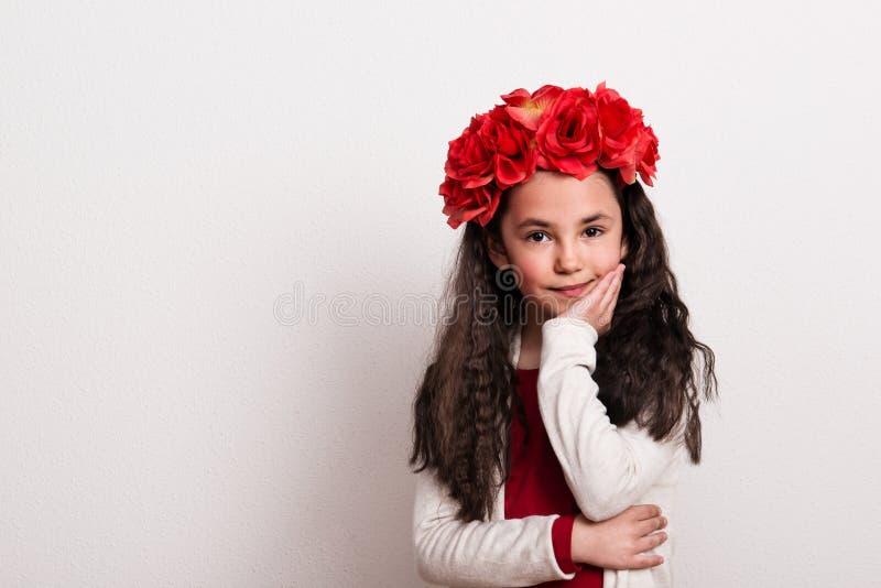 En liten flicka med blommahuvudbindelanseendet i en studio, haka som vilar på hennes hand arkivbilder