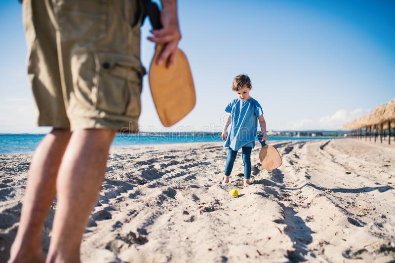 En liten flicka med den oigenkännliga fadern som utomhus spelar på sandstranden royaltyfria foton