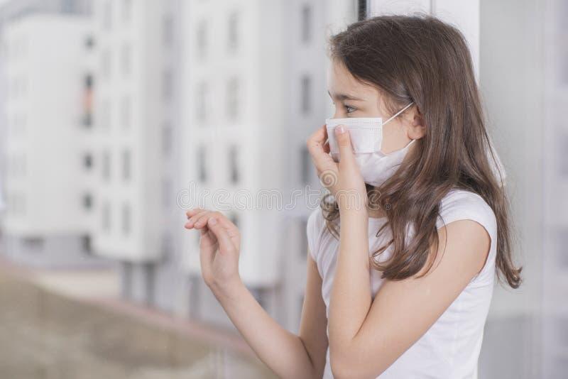 En liten flicka med mask för att skydda Covid-19 står nära fönstret och är ledsen Flickan blev sjuk och kan inte gå ut Wuhan arkivbild